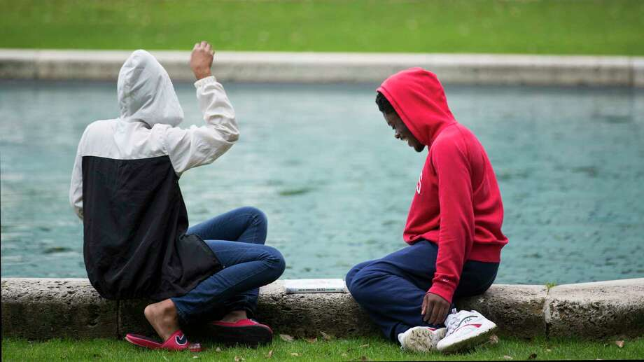 Becca Brown,left, and Korey Parker hang out by the City Hall reflection pool under cloudy skies on Thursday, Feb. 7, 2019, in Houston. Photo: Brett Coomer, Staff Photographer / © 2019 Houston Chronicle