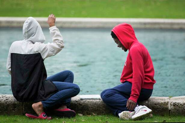Becca Brown,left, and Korey Parker hang out by the City Hall reflection pool under cloudy skies on Thursday, Feb. 7, 2019, in Houston.