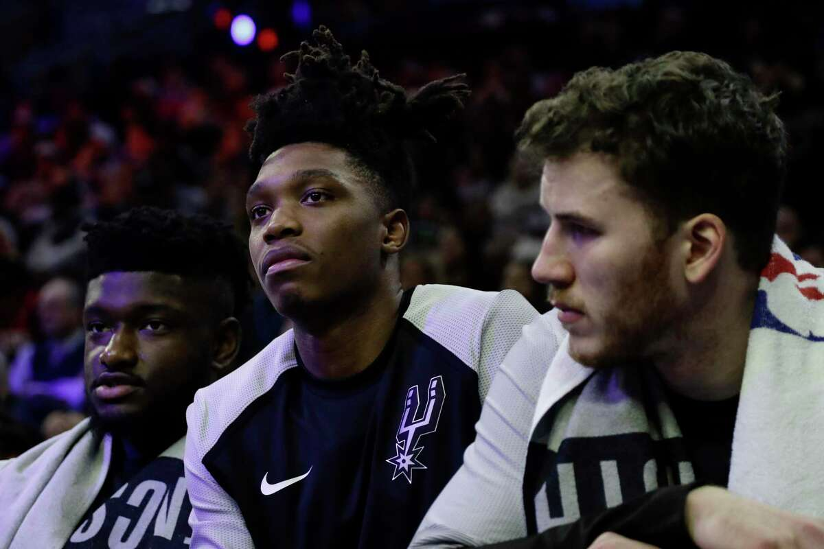 San Antonio Spurs' Lonnie Walker IV, center, watches from the bench during the first half of an NBA basketball game against the Philadelphia 76ers, Wednesday, Jan. 23, 2019, in Philadelphia. (AP Photo/Matt Slocum)