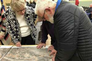 Residents look at maps of the proposed routes for the extension of the Sue Grossman Trail into downtown Torrington.