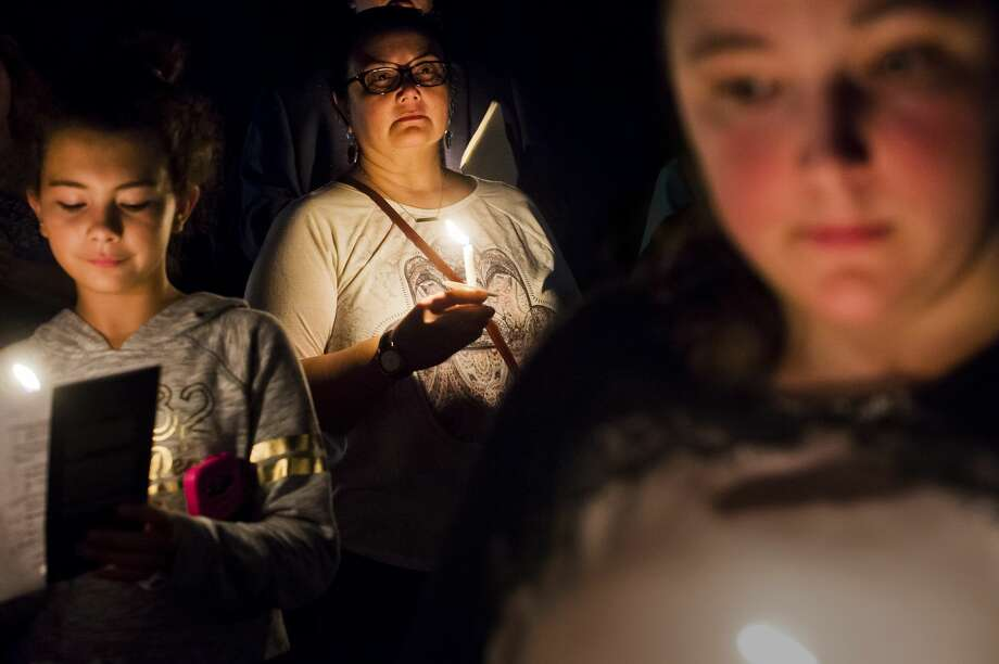 Kris Kernstock of Midland, center, observes a moment of silence during a candlelight vigil for victims of the mass shooting which took place Sunday, Oct. 1 in Las Vegas, on Tuesday, Oct. 3, 2017 at Unitarian Universalist Fellowship of Midland. About 60 people attended the vigil, which was organized by WOMAN (Women of Michigan Action Network) and the Great Lakes Bay Region Chapter of Moms Demand Action for Gun Sense in America. This photo took first place in the 2018 MPA Better Newspaper Contest Class C News Photo category. (Katy Kildee/kkildee@mdn.net) Photo: (Katy Kildee/kkildee@mdn.net)