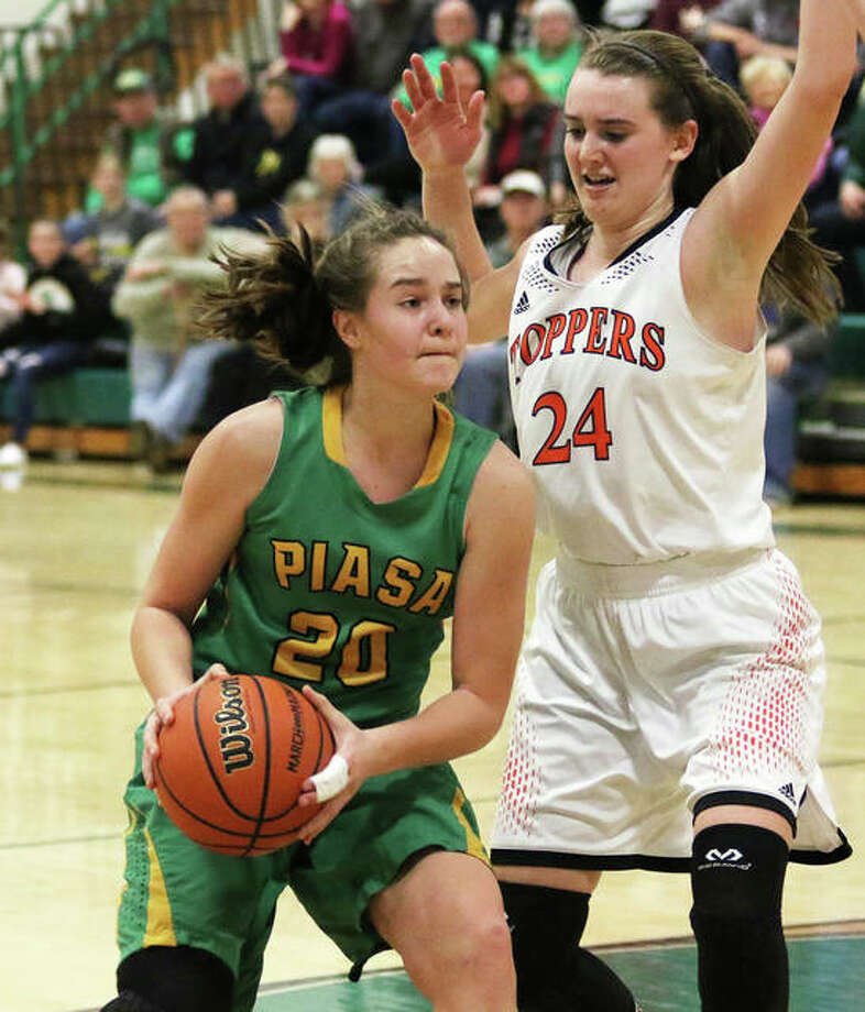Southwestern's Korrie Hopkins (left) drives on Hillsboro's Sammi Matoush before pulling up to hit a shot before the buzzer ending the third quarter Thursday night in the title game of the Southwestern Class 2A Regional in Piasa. Photo: Greg Shashack / The Telegraph