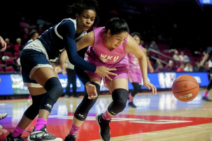 Rice's Jasmine Smith, left, and Western Kentucky's Meral Abdelgawad battle for a loose ball Thursday night. The Owls won 68-46 to stay atop Conference USA.