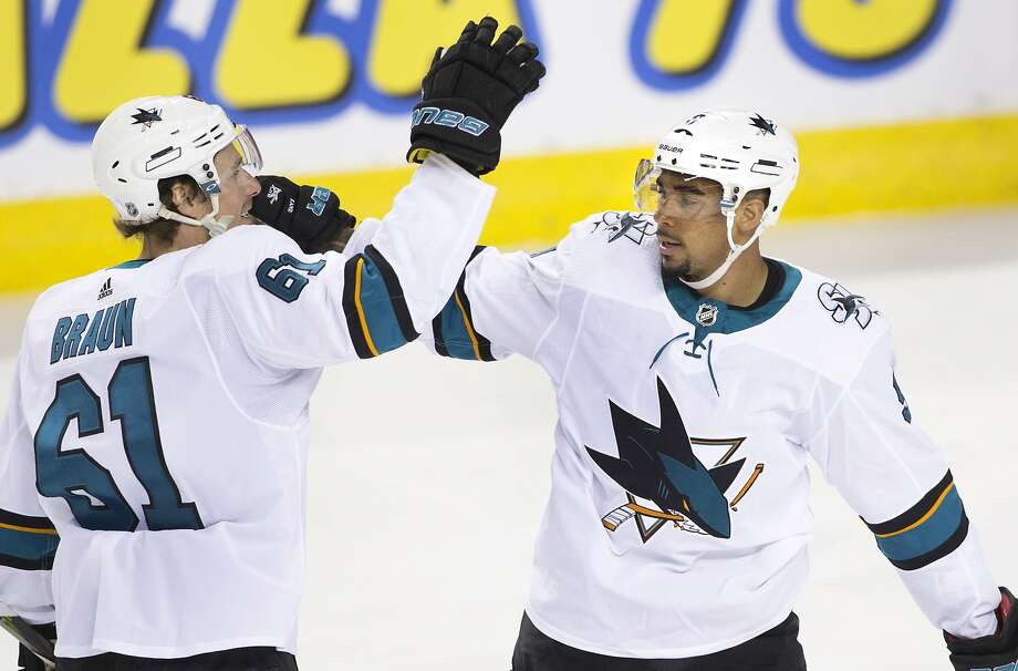 San Jose's Evander Kane (right) accepts the congratulations of teammate Justin Braun during the first period in Calgary. The Sharks moved within two points of Calgary in the division. Photo: Larry MacDougal / Canadian Press