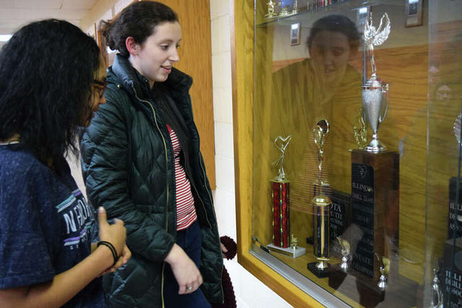 Taylor Caldwell (left) and Abbi Blanford find the trophies earned by the Jacksonville High School winter guard in a case at the school on Wednesday. The team returns to the state finals Saturday as defending champions in AA tall flag and AA lyrical flag. Photo: Rosalind Essig | Journal-Courier