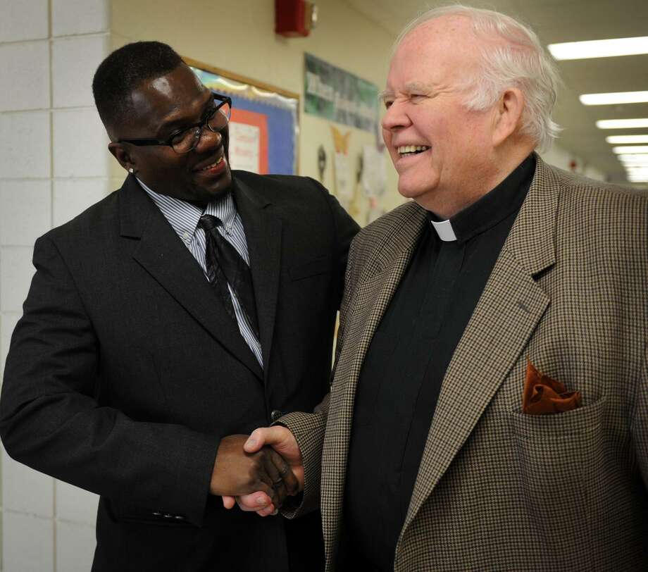 Former Notre Dame of Fairfield basketball and baseball star Tony Barr, left, shakes hands with school president Rev. William Sangiovanni during a visit to his former high school in Fairfield, Conn. on Thursday, May 2, 2013. Barr served over twenty years in prison for drug trafficking. Photo: Brian A. Pounds / Brian A. Pounds / Connecticut Post