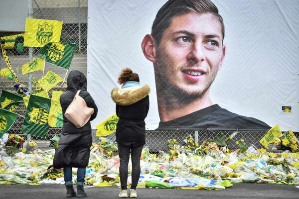 People look at yellow flowers displayed in front of the portrait of Argentinian forward Emiliano Sala at the Beaujoire stadium in Nantes, on February 8, 2019. - FC Nantes football club announced on February 8, 2019 that it will freeze the #9 jersey as a tribute to Cardiff City and former Nantes footballer Emiliano Sala who died in a plane crash in the English Channel on January 21, 2019. (Photo by LOIC VENANCE / AFP)LOIC VENANCE/AFP/Getty Images