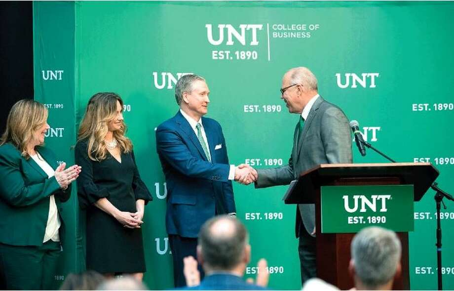 University of North Texas president Neal Smatresk, right, shakes the hand of alum G. Brint Ryan, center, chair of the UNT Board of Regents who donated $30 million to create the G. Brint Ryan College of Business. The university announced the donation on Monday. On the left is UNT College of Business Dean Marilyn Wiley, and Ryan's wife, Amanda. Photo: Ranjani Groth/UNT Photo