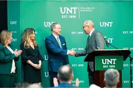 University of North Texas president Neal Smatresk, right, shakes the hand of alum G. Brint Ryan, center, chair of the UNT Board of Regents who donated $30 million to create the G. Brint Ryan College of Business. The university announced the donation on Monday. On the left is UNT College of Business Dean Marilyn Wiley, and Ryan's wife, Amanda.