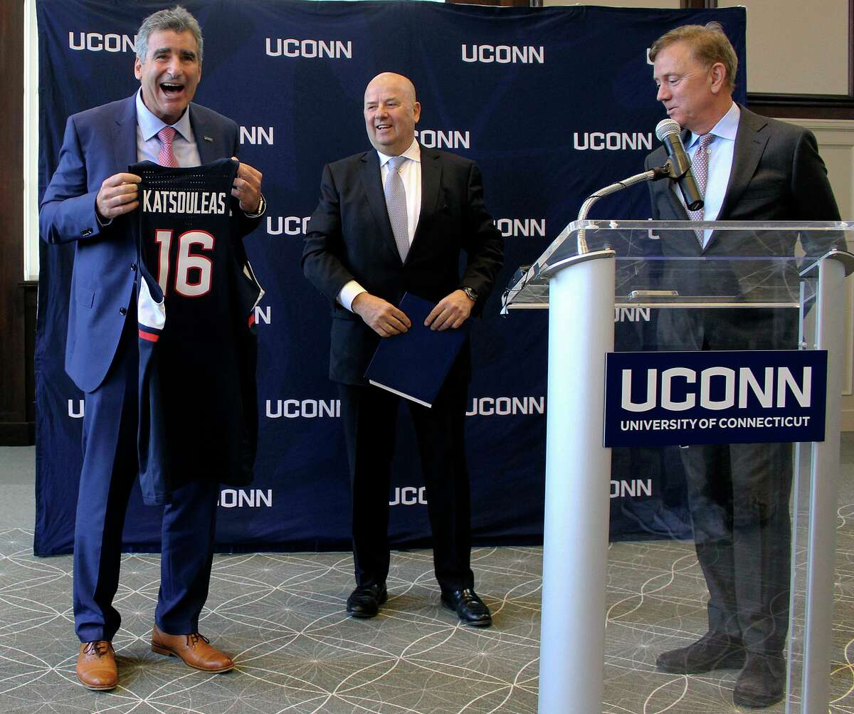 Thomas Katsouleas, left, is presented with a UConn basketball jersey by University of Connecticut Board of Trustees chairman Thomas Kruger, center, and Connecticut Gov. Ned Lamont after being appointed as the University of Connecticut's 16th president on Tuesday, Feb. 5, 2019 in Storrs, Conn.