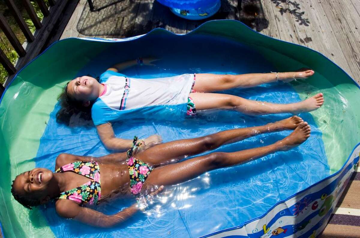 Olivia DeLuca, 8, and Chloe, 8, submerge themselves in water on a hot afternoon at the DeLuca's home Thursday, July 22, 2010. This is the second year that Chloe has spent time with the Deluca family as part of the Fresh Air Fund.