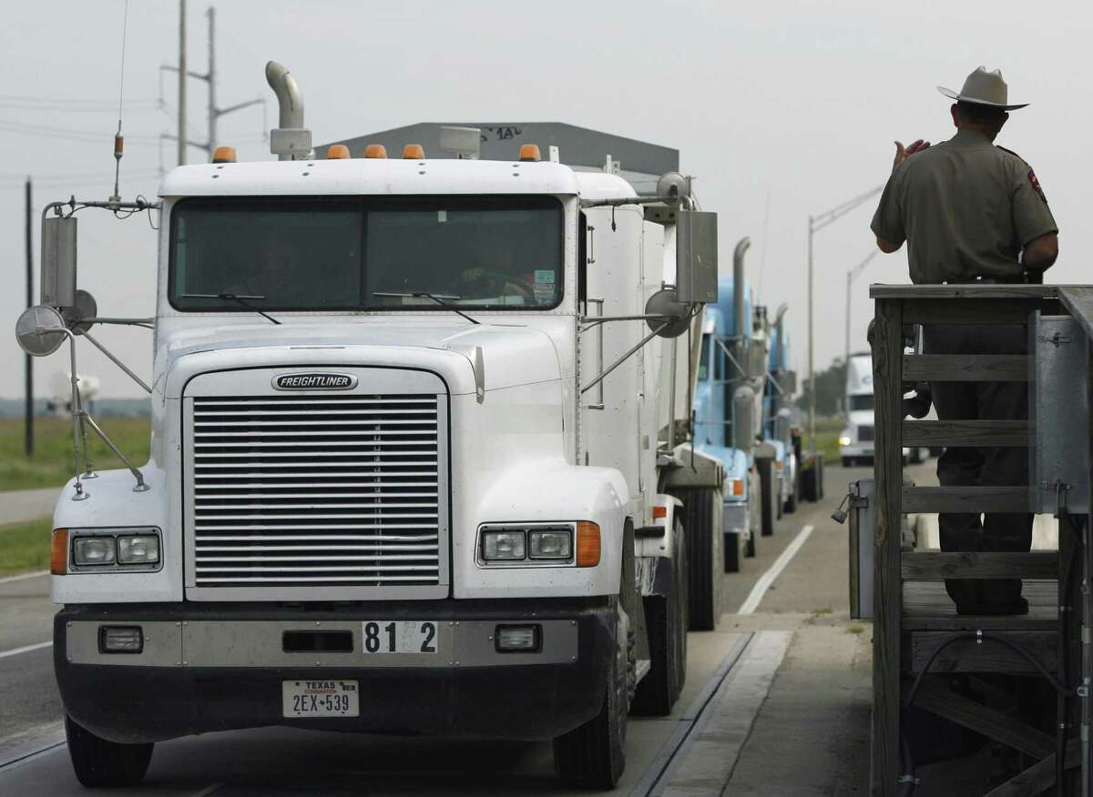 In this file photo, a Texas Department of Public Safety trooper motions a trucker off the scales at an Interstate 35 weigh station in San Marcos. More than a half-million overweight trucks are allowed onto the nation's roads and bridges.