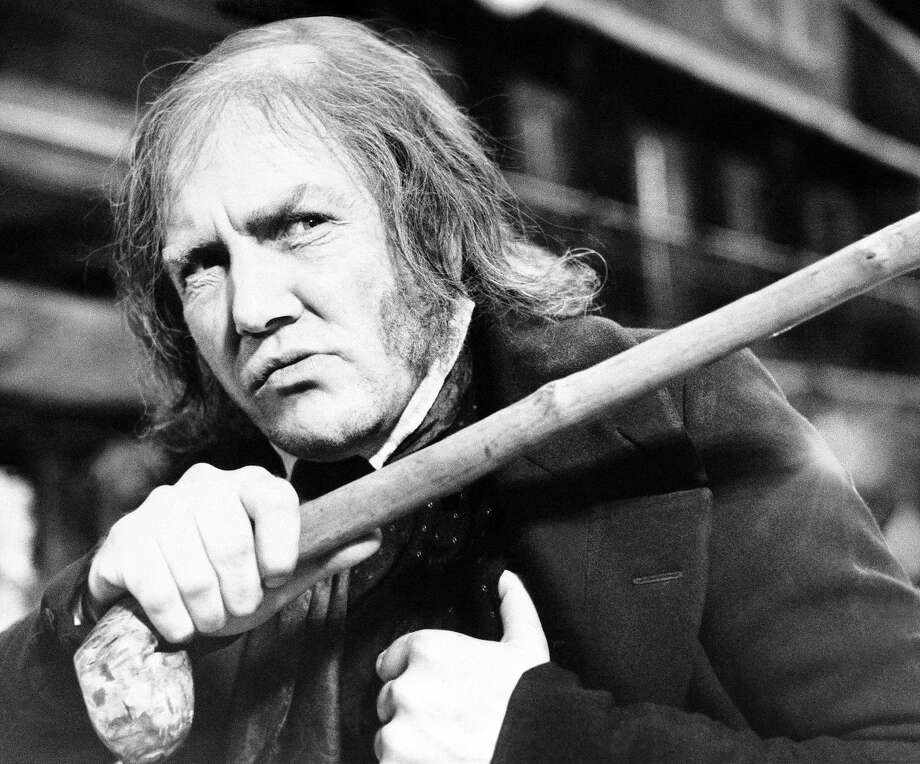 "British actor Albert Finney waves a cane while playing the title role in the 1970 film ""Scrooge."" Photo: R. Dear / Associated Press 1970"