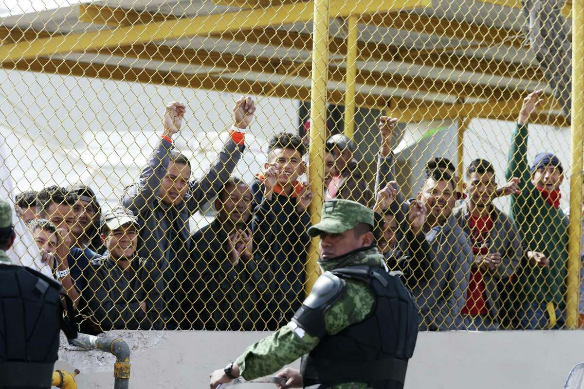 Immigrants line the fence taunting immigrants boarding a bus who signed self-deportation papers at a shelter in Piedras Negras, Mexico on Thursday. Columnist Michael Taylor takes a look at the immigration issue from the aspect of the economic impact on Texas.