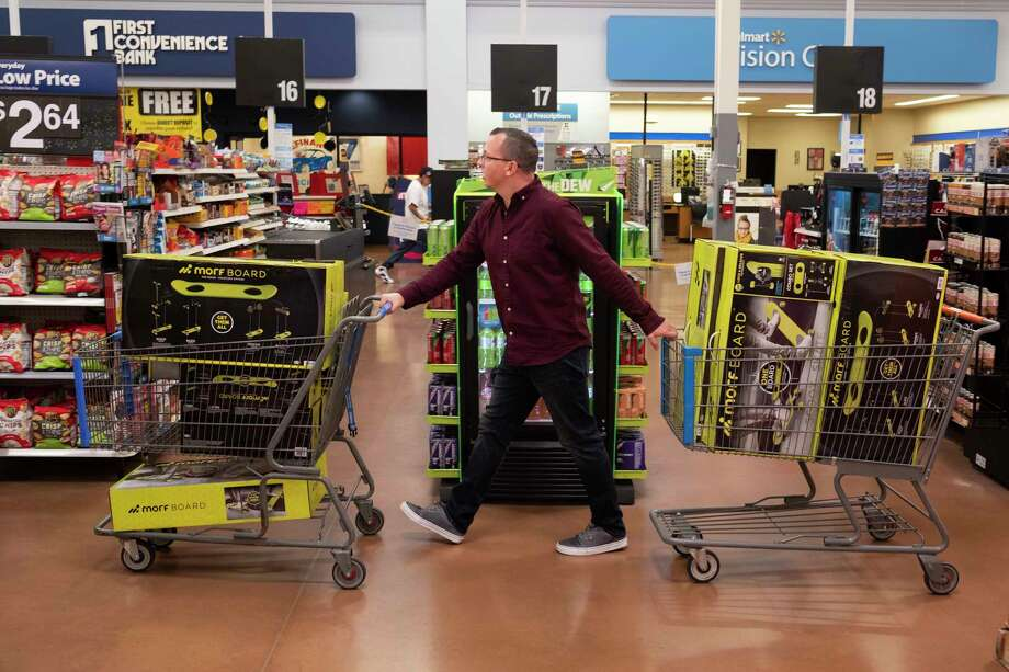 Juston Herbert pushes two carts of Morf Boards, a popular kids toy, through a Walmart in Phoenix. Photo: Photo For The Washington Post By Dominic Valente. / Dominic Valente for The Washington Post