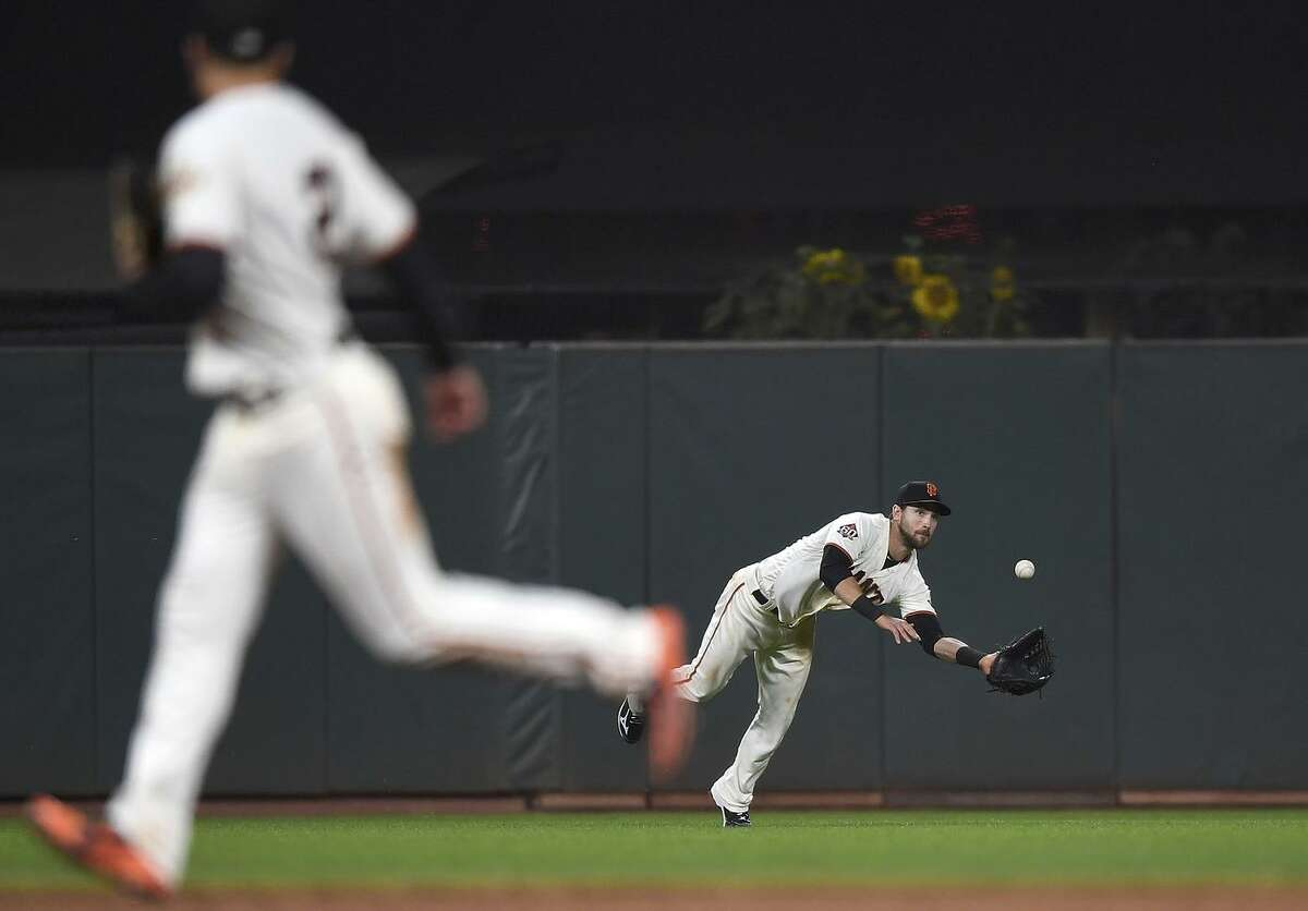 Steven Duggar #6 of the San Francisco Giants dives for the ball that goes for a triple off the bat of Brad Miller #10 of the Milwaukee Brewers in the top of the six inning at AT&T Park on July 26, 2018 in San Francisco, California.