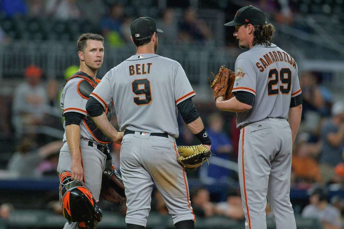 Giants catcher Buster Posey (left), first baseman Brandon Belt (9), and starting pitcher Jeff Samardzija (29) meet at the mound to talk strategy during a game between the Atlanta Braves and San Francisco Giants on June 21, 2017 at SunTrust Park in Atlanta, GA. The Atlanta Braves beat the San Francisco Giants 5 3 in extra innings.