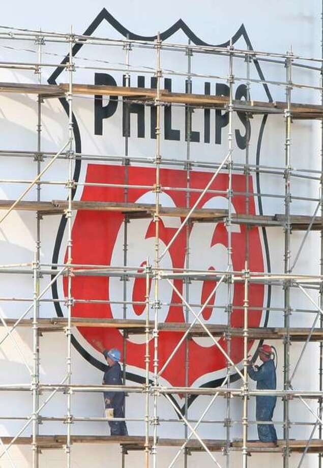 Workers add a Phillips 66 logo to a tank in Roxana. In this Telegraph file photo. The Wood River Refinery processes crude oils to make gasoline, diesel and jet fuel, petrochemical feedstocks and asphalt. Photo: John Badman | Telegraph File Photo