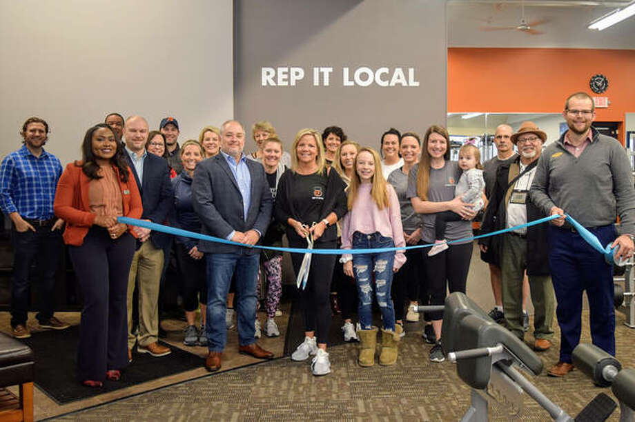 The Edwardsville/Glen Carbon Chamber of Commerce sponsored a ribbon-cutting at E'ville Fitness Wednesday. The gym is locally owned by Eric and Carie Terry and located at 235 Harvard Drive. The Terrys are in the middle, surrounded by family, friends and chamber of commerce members. Photo: For The Intelligencer