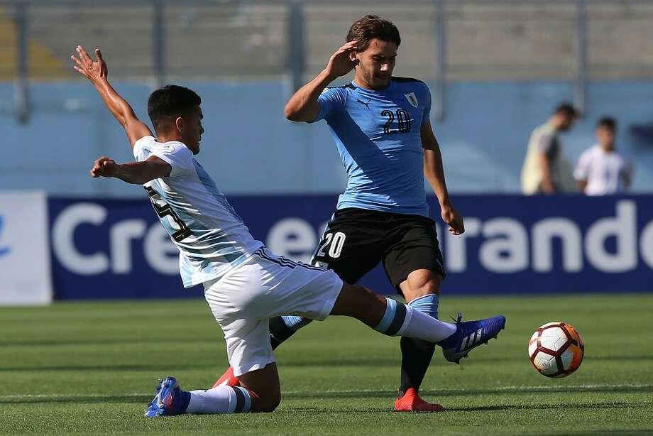 Pedro de la Vega (izq.) rechaza la pelota frente a  Juan Boselli en el triunfo de Argentina por 2-1 frente a Uruguay el jueves 7 de febrero de 2019 en estadio El Teniente de Rancagua, Chile. Photo: AFP/Getty Images