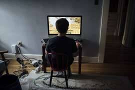 """FILE -- A boy plays Minecraft while waiting for dinner at his home in Cleveland Heights, Ohio, Oct. 1, 2018. A study on screen time featured on """"60 Minutes"""" is sure to alarm parents. Here's what scientists know, and don't know, about the link between screens, behavior, and development.  (Dustin Franz/The New York Times)"""
