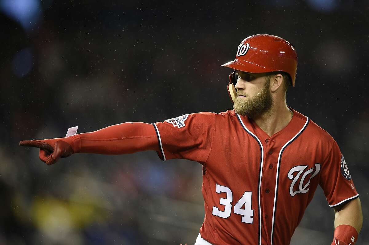 FILE - In this Sept. 8, 2018, file photo, Washington Nationals' Bryce Harper pointing to the dugout after he hit a two-run home run during the seventh inning of the second baseball game of a doubleheader against the Chicago Cubs, in Washington. As the start of spring training approaches, the Washington Nationals are waiting right along with the rest of the world to find out where Harper will be playing next season. (AP Photo/Nick Wass, File)