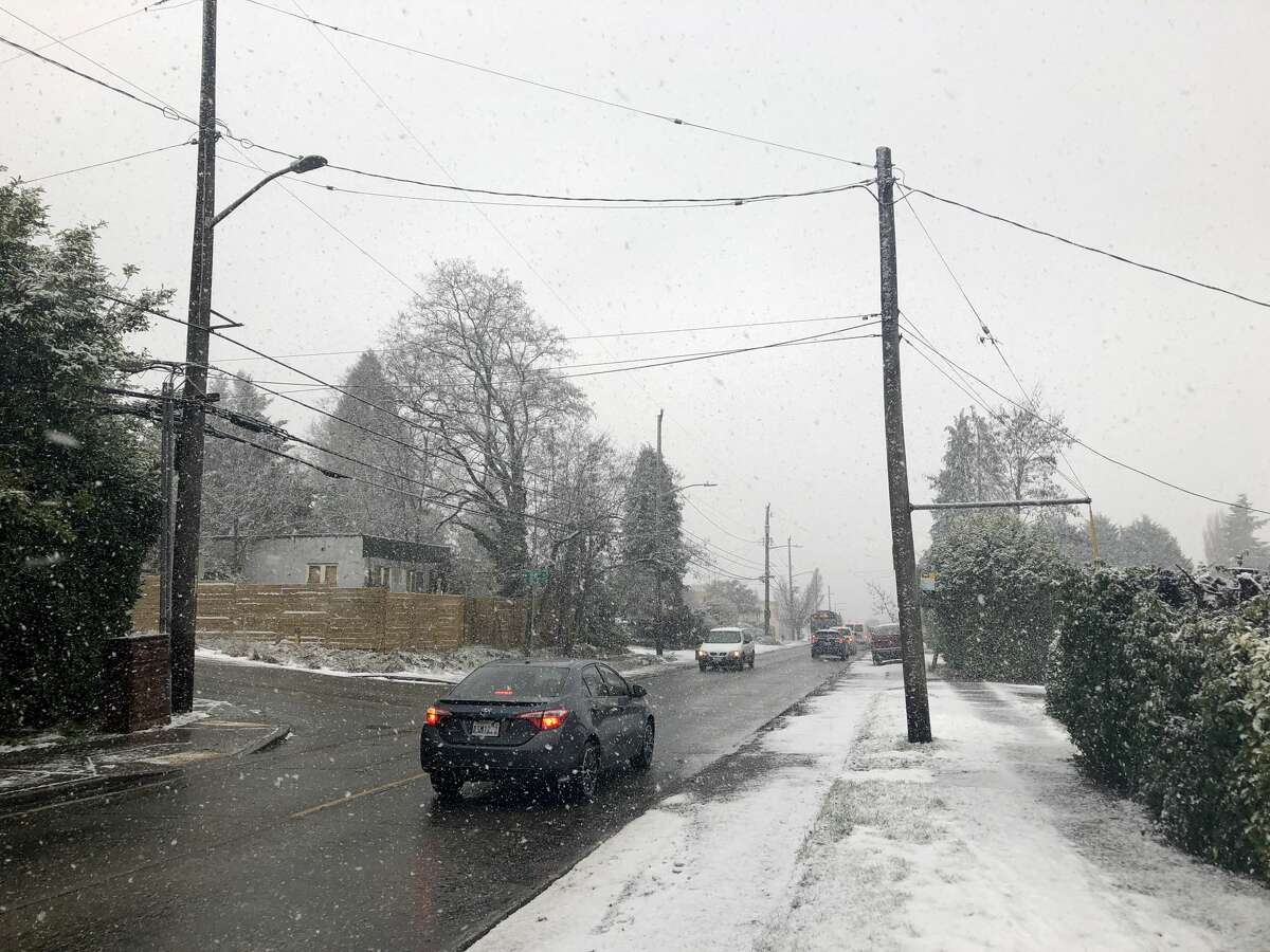 Snow starts falling heavily along 35th Avenue SW in West Seattle shortly after noon Friday. The National Weather Service expected up to 8 inches to pile up before the storm eased Saturday.