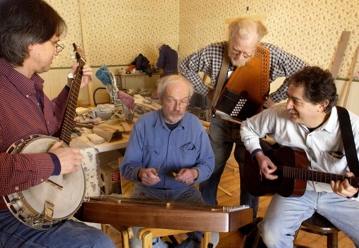Old Songs folk-arts organization musicians, Roger Mock, left, Bill Spence, Gene Langley, and Phil Teumin, right, take a break from renovations on the Old Songs House in Voorheesville, for a quick jam session in the former church on Thursday, Jan. 29, 2004, in Voorheesville, N.Y. (Will Waldron/Times Union)