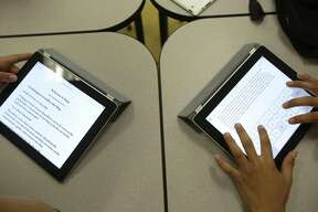 Students use iPads to write research papers at Hawthorne Academy, a prekindergarten through eighth grade academy in the San Antonio Independent School District.