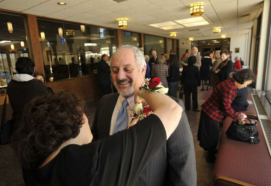 Gail Conti pins a corsage on her husband, Frank, before the Anniversary Mass at St. Leo Catholic Church in Stamford on Sunday, Feb. 10, 2013. The Contis will be celebrating their 25-year wedding anniversary this May. Photo: Jason Rearick / The Stamford Advocate / The News-Times