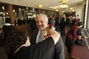 Gail Conti pins a corsage on her husband, Frank, before the Anniversary Mass at St. Leo Catholic Church in Stamford on Sunday, Feb. 10, 2013. The Contis will be celebrating their 25-year wedding anniversary this May.