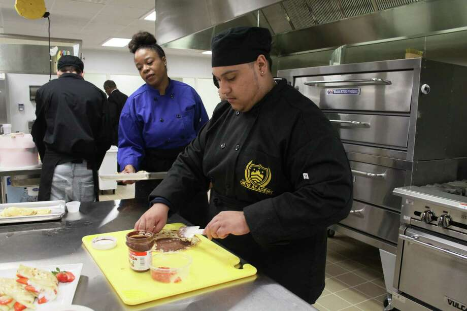 Omar Lopez, 18, spreads Nutella on a crepe he made as part of his culinary arts class as his teacher Quindetta Thomas, takes a tray. Lopez is a student at Fortis Academy, the first rehabilitation high school in Harris County. Photo: Mayra Cruz