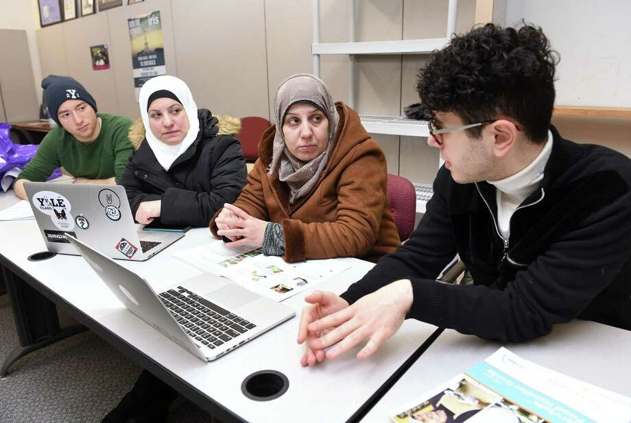 Yale University first-year student Mourad Frishkopf, left, and junior Nour Hussari, right explain the ordering system for the organization Havenly Treats to Syrian refugees Faten Natfaji, center left, and Hala Ghali, center right, at the offices of Integrated Refugee and Immigrant Services in New Haven on Feb. 1. Photo: Arnold Gold / Hearst Connecticut Media / New Haven Register