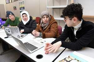 Yale University first-year student Mourad Frishkopf, left, and junior Nour Hussari, right explain the ordering system for the organization Havenly Treats to Syrian refugees Faten Natfaji, center left, and Hala Ghali, center right, at the offices of Integrated Refugee and Immigrant Services in New Haven on Feb. 1.