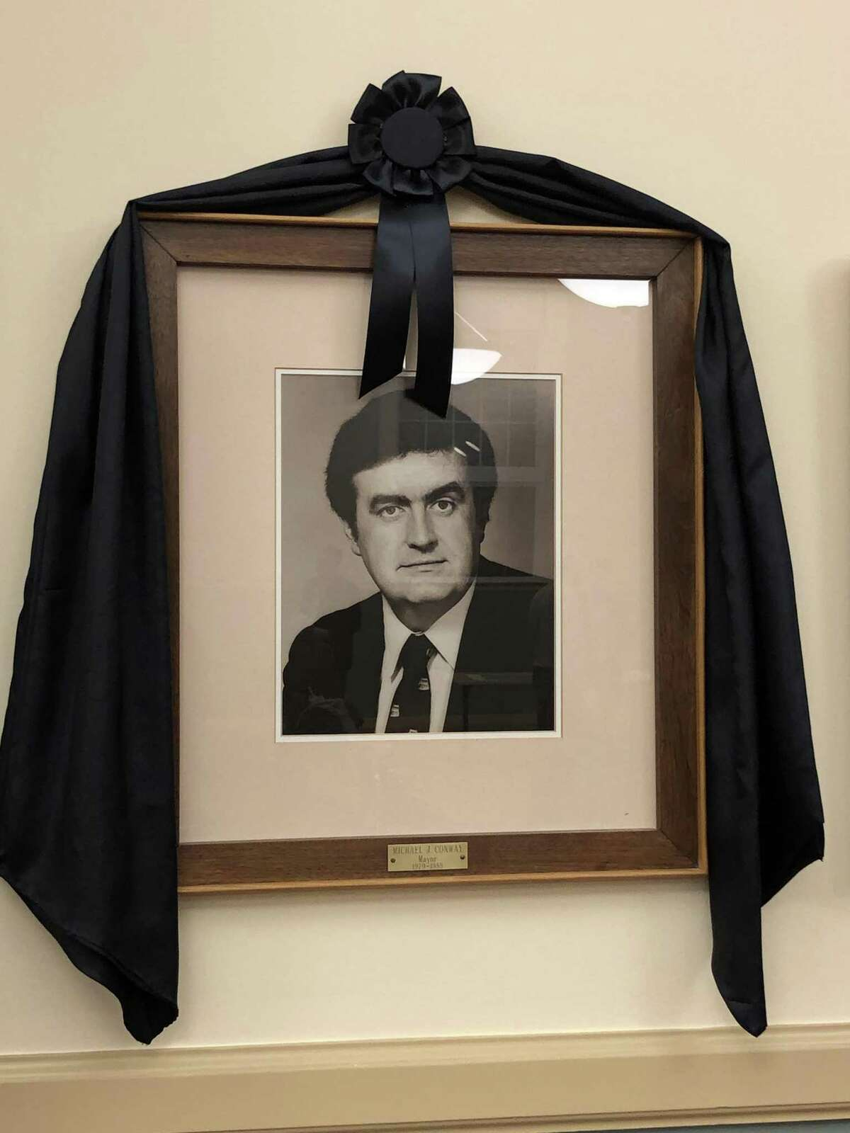 A portrait of former Mayor Michael J. Conway Jr., draped with memorial bunting, is displayed in the City Hall Auditorium.