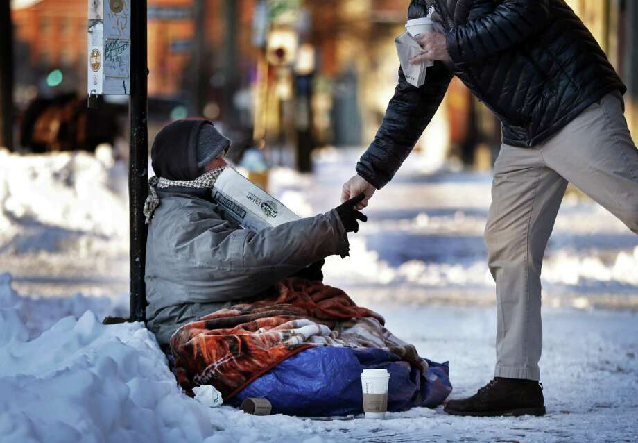 A homeless man outside a coffee shop accepts cash from a customer on a bitter cold morning in Portland, Maine. Instead of helping those crossing the border find asylum, a reader suggests aiding downtrodden Americans. Photo: Robert F. Bukaty /Associated Press / Copyright 2019 The Associated Press. All rights reserved.