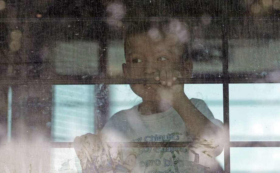 An immigrant child looks out from a U.S. Border Patrol bus leaving as protesters block the street outside the U.S. Border Patrol Central Processing Center in McAllen June 23. Immigrant children described hunger, cold and fear in a voluminous court filing about the facilities where they were held in the days after crossing the border. Photo: David J. Phillip /Associated Press / Copyright 2018 The Associated Press. All rights reserved.