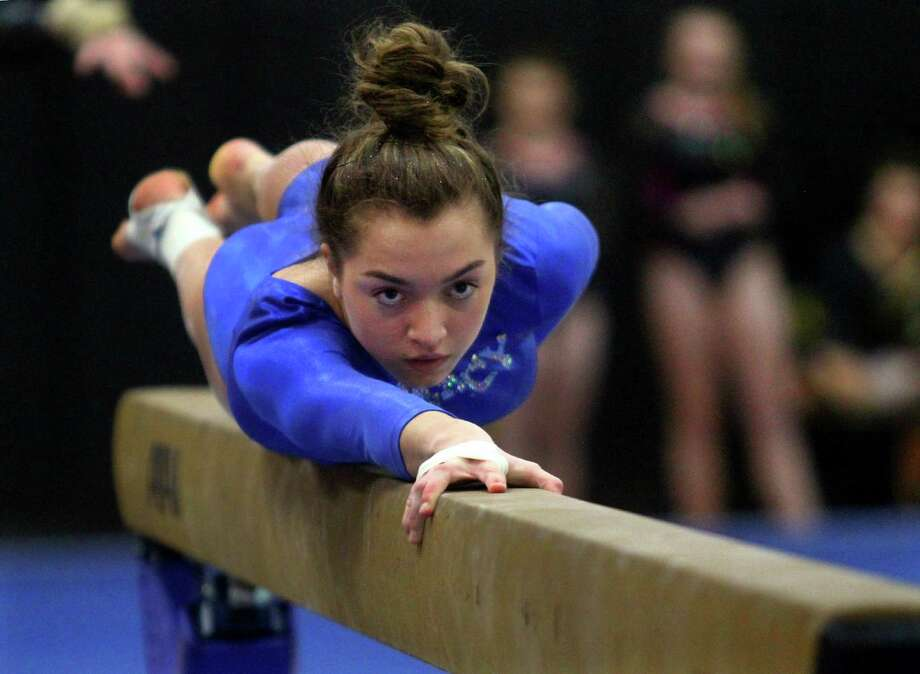Mercy's Mia Lawrence competes on the balance beam during the SCC gymnastics championship Thursday. Photo: Christian Abraham / Hearst Connecticut Media / Connecticut Post