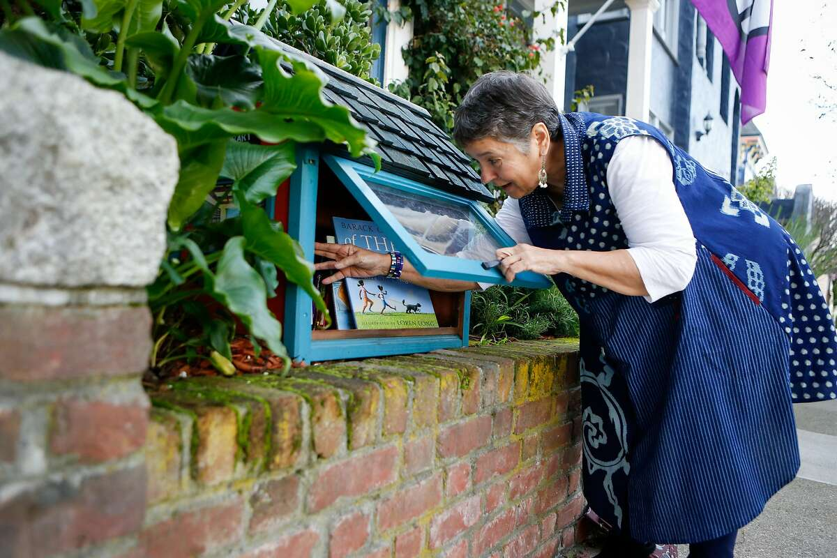 Marc Coronado adjusts the placement of books in her small neighborhood library box on Thursday, February 7, 2019 in Bernal Heights San Francisco, Calif.