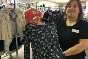 Clothed by Faith recently opened a new section in its expanded space at 802 Dominion Drive, Suite 100. That space includes an area where women clients may shop for clothes they need said Rebecca Earnshaw, executive assistant. marketing, events & development manager, as she displays one of the tops from that section.