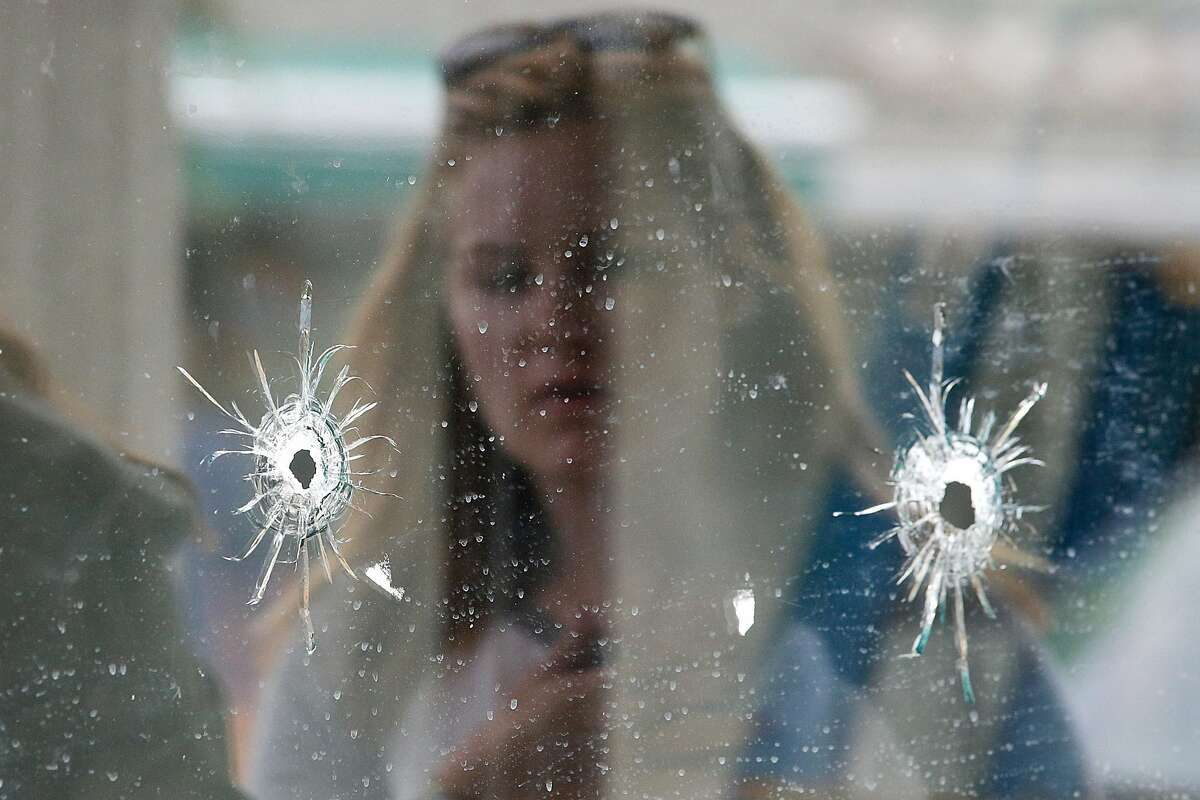 A woman looks at the bullet holes on the window of IV Deli Mark where Friday night's mass shooting took place by a drive-by shooter on Saturday, May 24, 2014, in Isla Vista, Calif. The shooter went on a rampage near a Santa Barbara university campus that left seven people dead, including the attacker, and seven others wounded, authorities said Saturday. Attorney Alan Shifman says the family of a man suspected in the shooting rampage called police several weeks ago after being alarmed by YouTube videos