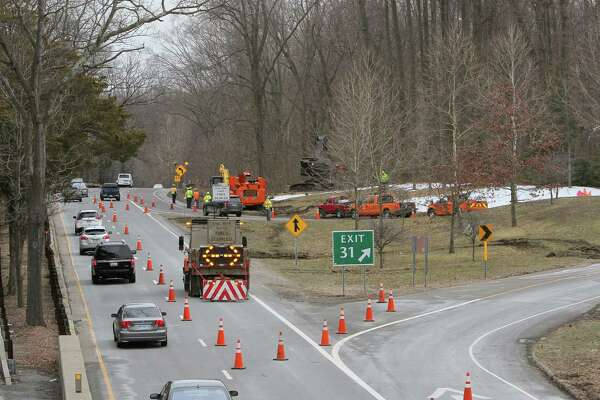 A crew from the Connecticut Department of Transportation clear trees along the Northbound Merritt Parkway at exit #31 for North Street in Greenwich, Conn. on Tuesday, March 27, 2018. The work has been twice delayed because of winter storms. Traffic control personnel and signing patterns will be utilized to guide motorists through the work zone, which is expected to last thru the week.