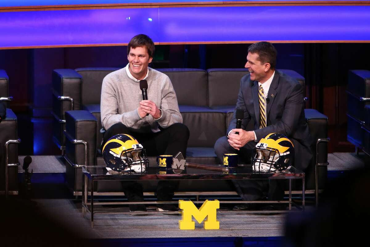 Tom Brady, former Michigan Wolverine and current NFL quarterback talks with Head coach Jim Harbaugh of the Michigan Wolverines during the Michigan Signing of the Stars event at Hill Auditorium on February 3, 2016 in Ann Arbor, Michigan.