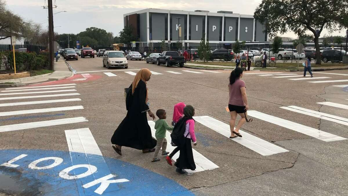 Children and parents cross De Moss and Tarnef streets, one of the dangerous intersections in the Gulfton neighborhood, on Feb. 4.