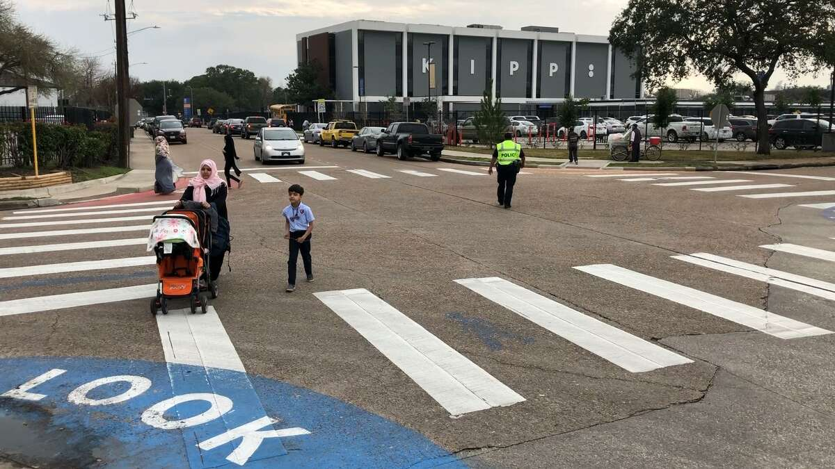 A Houston Police Officer directs children and parents across De Moss and Tarnef streets, one of the dangerous intersections in the Gulfton neighborhood, on Feb. 4.