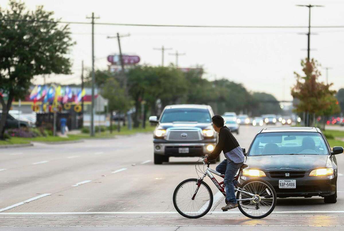 A bicyclist crosses the intersection of Gessner Road and Bellaire Boulevard on Oct. 31, 2018.