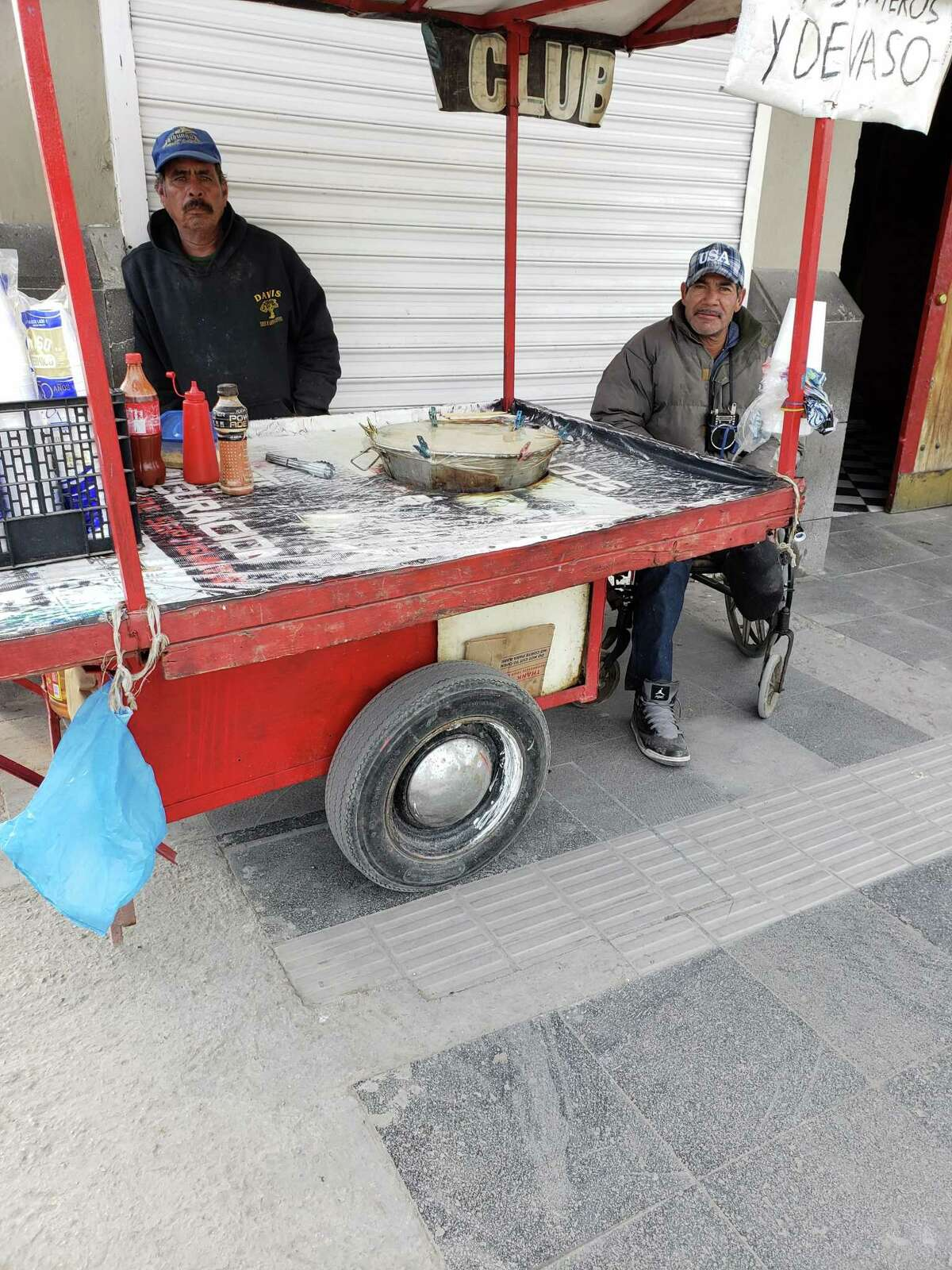 Two men tend to a food cart in Juarez, Mexico.