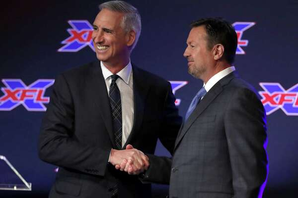 Oliver Luck, XFL Commissioner and CEO greets Bob Stoops after Luck introduced during a news conference as the new general manager and head coach of the Dallas XFL football team in Arlington, Texas, Thursday, Feb. 7, 2019. (AP Photo/Tony Gutierrez)