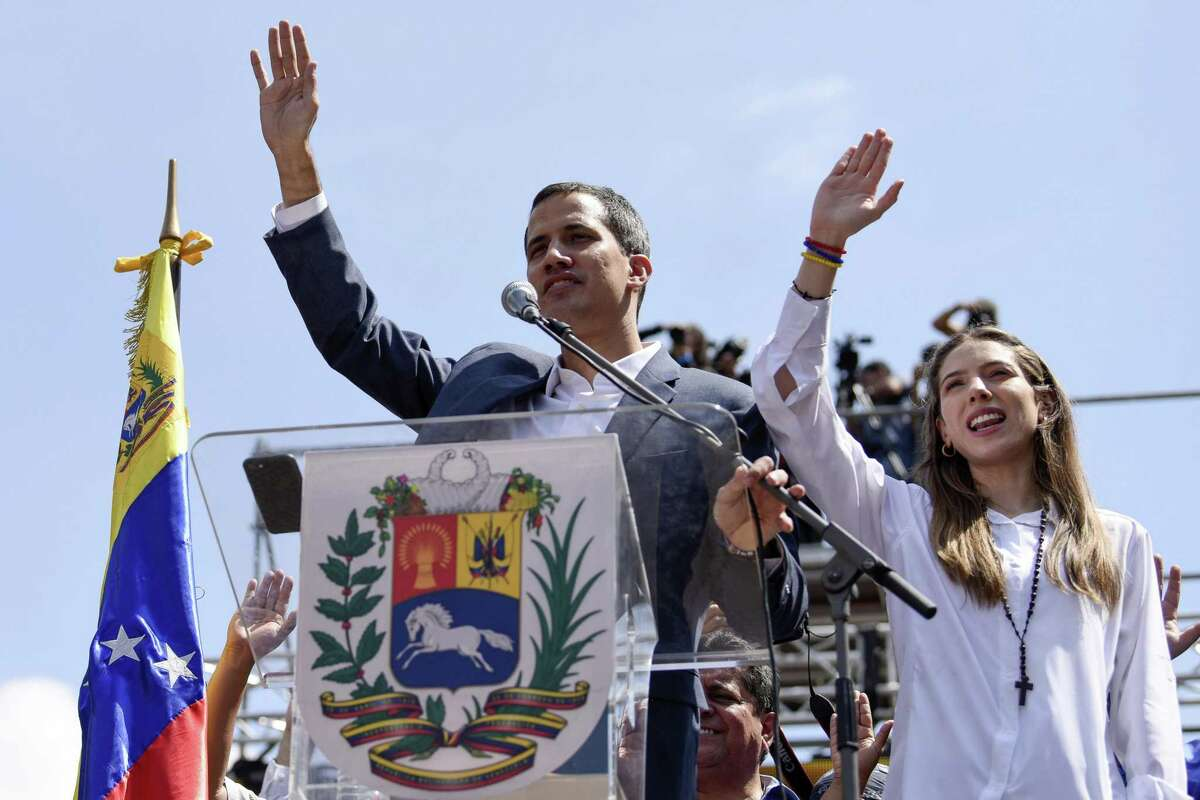 Juan Guaido, president of the National Assembly who swore himself in as the leader of Venezuela, and his wife, Fabiana Rosales, raise their hands during a pro-opposition protest in Caracas, Venezuela, on Feb. 2, 2019. MUST CREDIT: Bloomberg photo by Carlos Becerra