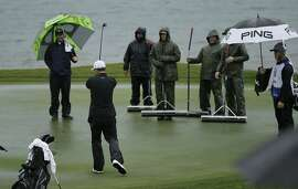 Egon Durban reacts after making a putt on the rain-soaked 18th green of the Pebble Beach Golf Links as greenskeepers watch, during the second round of the AT&T Pebble Beach Pro-Am golf tournament Friday, Feb. 8, 2019, in Pebble Beach, Calif. (AP Photo/Eric Risberg)